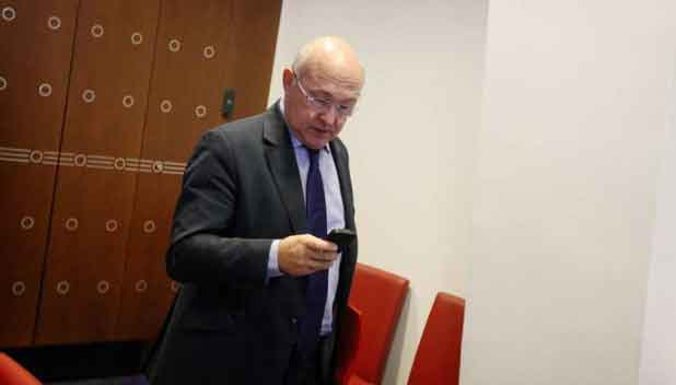 Michel Sapin en train d'utiliser son smartphone.