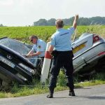 Des gendarmes près de deux voitures accidentées.