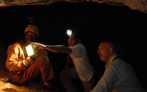 Le chercheur français Laurent Bruxelles (centre) et le professeur Ron Clarke (droite) dans une grotte du site de Sterkfontein (AP).