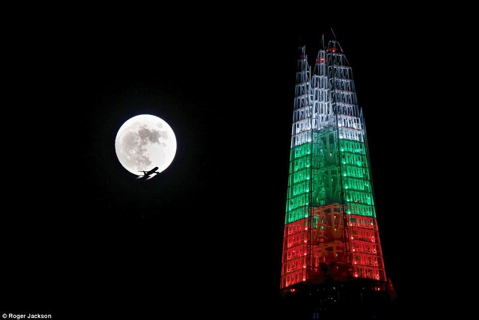 Un avion vole devant la pleine Lune froide qui illumine le ciel de Londres le soir de Noël. Même la tour Shard fait pâle figure à côté.