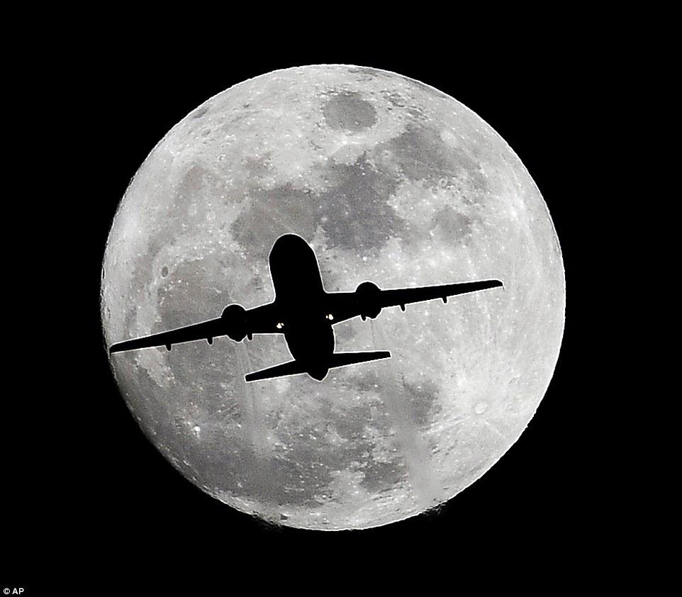 Un avion traversant la pleine Lune le soir de Noël alors qu'il se dirige vers l'aéroport International de Los Angeles