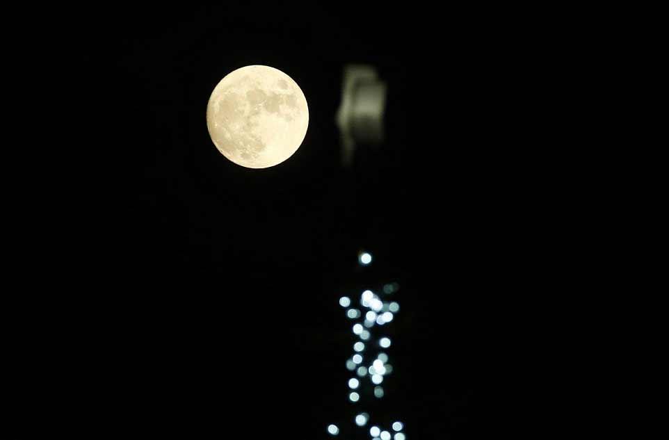 La pleine Lune se lève au-dessus d'un arbre de Noël décoré à Trafalgar Square, le soir de Noël