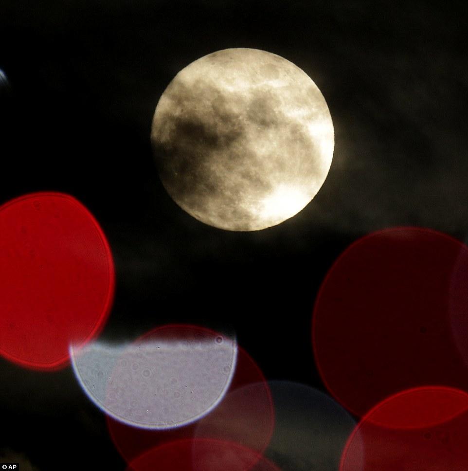 La Lune, presque pleine, entre les lumières des éclairages de Noël à Lenexa, au Kansas, la veille de Noël