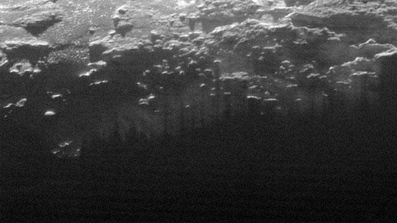 Sur ce détail de l'image générale, le soleil couchant illumine du brouillard, ou des brumes de basse altitude, avec des traces parallèles laissées par l'ombre des montagnes et des collines.