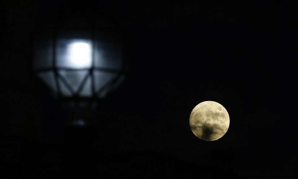 La lune se lève à travers un bout de nuage, à côté d'un lampadaire à Trafalgar Square (Londres)