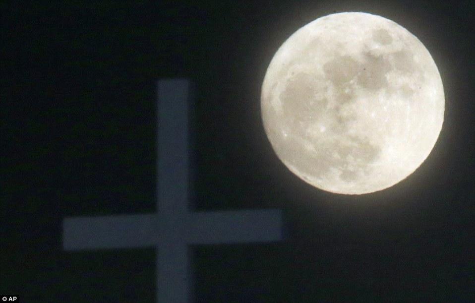 The_Long_Night_Moon_rises_behind_a_cross_at_Christ_Community_Chu
