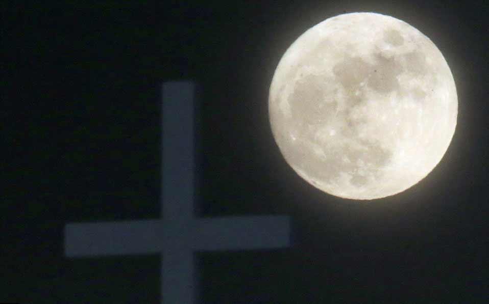 La lune derrière la croix de la Christ Community Church à Lawrence, Kansas