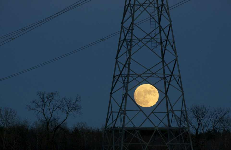 La pleine lune derrière un pylône électrique à Ottawa