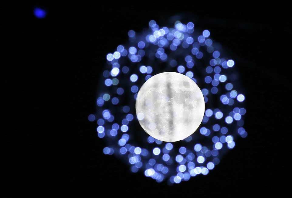 La lune pleine lune vue à travers les décorations de la place Oktyabrskaya à Minsk.