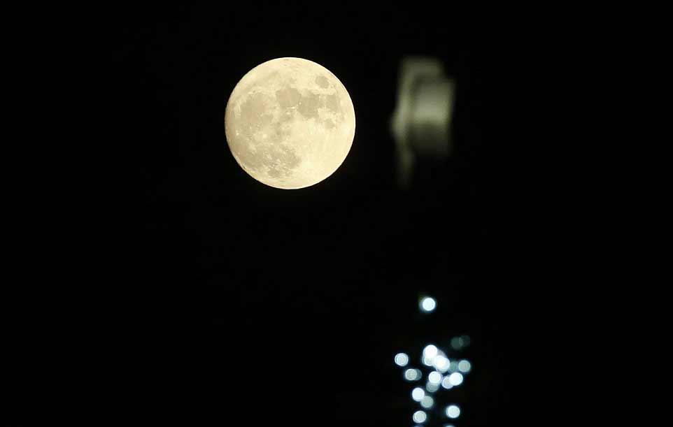 La pleine Lune se levant à côté de la Bourse de Londres.