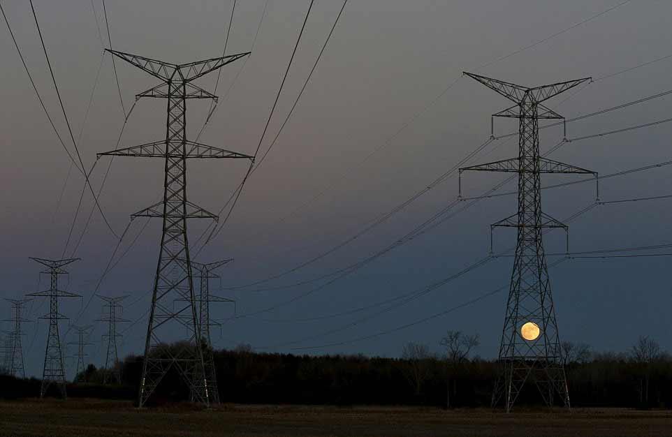 La pleine Lune se lève derrière un pylône électrique à Ottawa