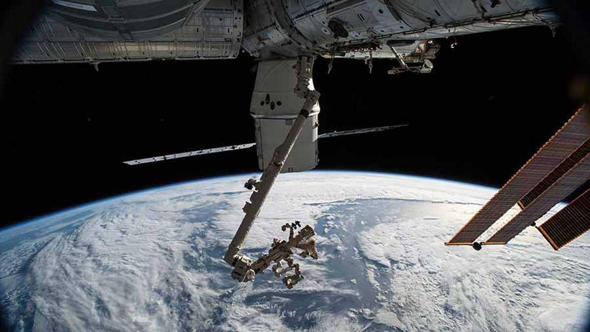 Le vaisseau de ravitaillement SpaceX Dragon et le bras robotique Canadarm2 avec le manipulateur adroit à usage spécial, Dextre, sont illustrés comme la station spatiale orbitant au-dessus du golfe d'Alaska.