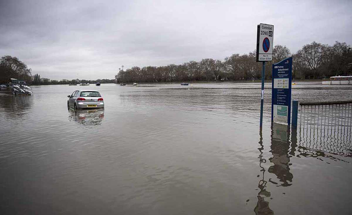 Une voiture est partiellement submergée après que l'eau du sol ait recouvert de nombreuses routes autour du remblai de Putney à l'ouest de Londres après que la Tamise ait rompu ses berges.