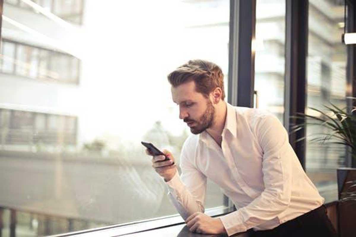 Un homme qui regarde son téléphone portable à côté d'une fenêtre