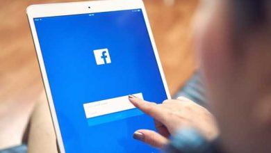 Une fille appuie sur l'écran d'un ordinateur en se connectant sur Facebook