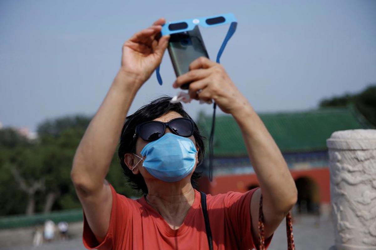 Eclipse solaire : une femme portant un masque en raison de la pandémie de coronavirus ou tenant des lunettes de protection devant son téléphone alors qu'elle capture l'éclipse partielle de soleil dans le parc du Temple du Ciel à Pékin.
