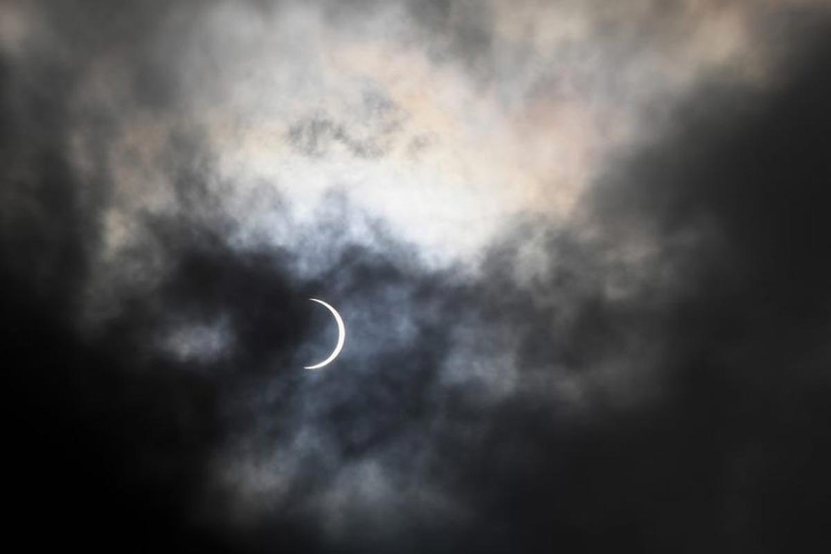 La lune couvre partiellement le soleil pendant l'éclipse solaire annulaire, vue à travers les nuages depuis Karachi.