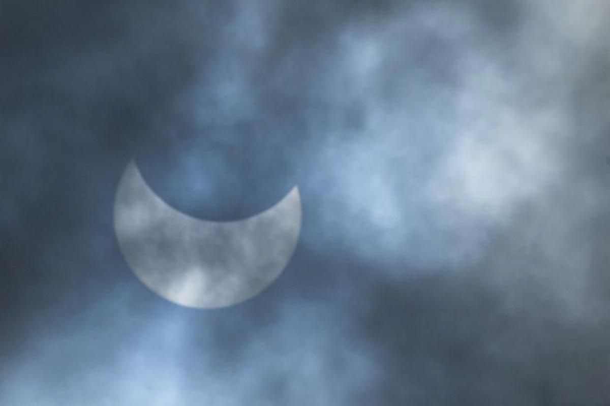 La lune se déplace devant le soleil lors d'une éclipse solaire annulaire vue à travers les nuages à Dhaka.