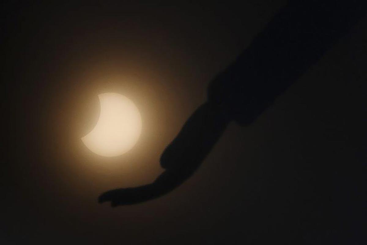 La lune se déplace devant le soleil pendant l'éclipse solaire annulaire, vue à travers les nuages depuis Chennai.