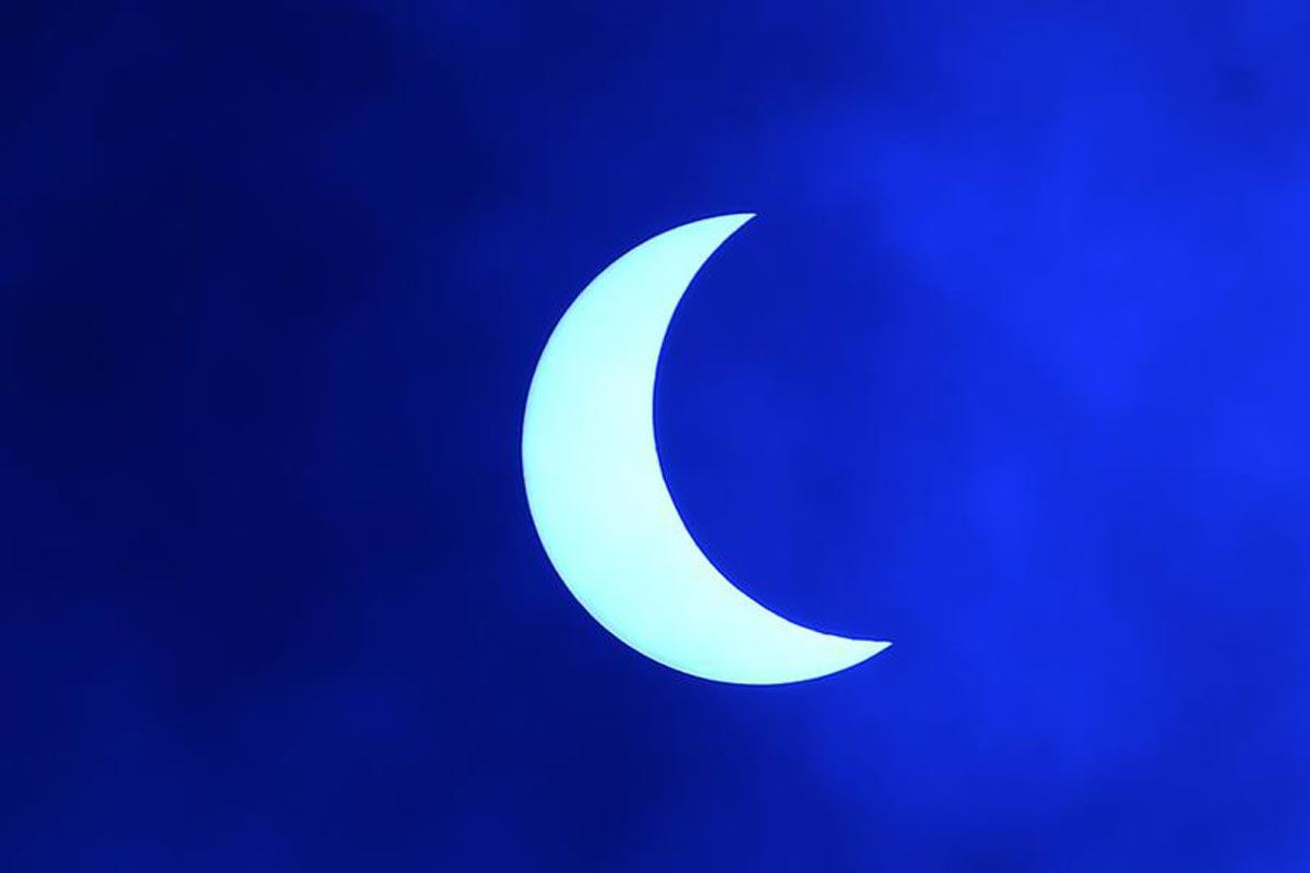 La lune se déplace devant le soleil pendant l'éclipse solaire annulaire, vue à travers les nuages depuis Katmandou.