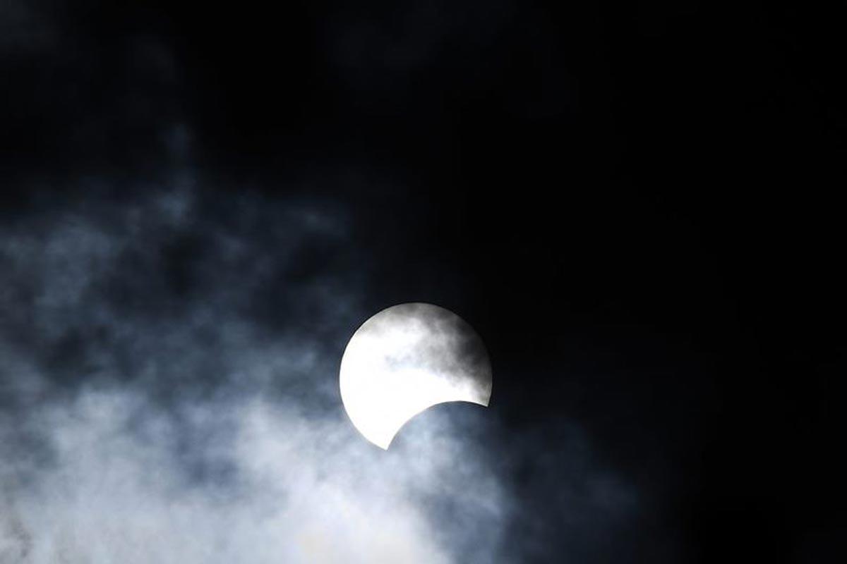 La lune se déplace devant le soleil pendant L'éclipse solaire annulaire vue à travers les nuages depuis Hanoi.