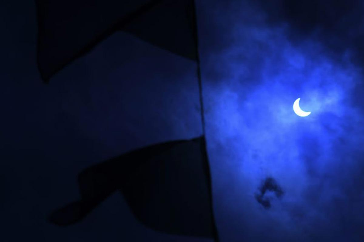 La lune se déplace devant le soleil pendant l'éclipse solaire annulaire, comme le montrent les drapeaux de prière de Katmandou à travers les nuages.