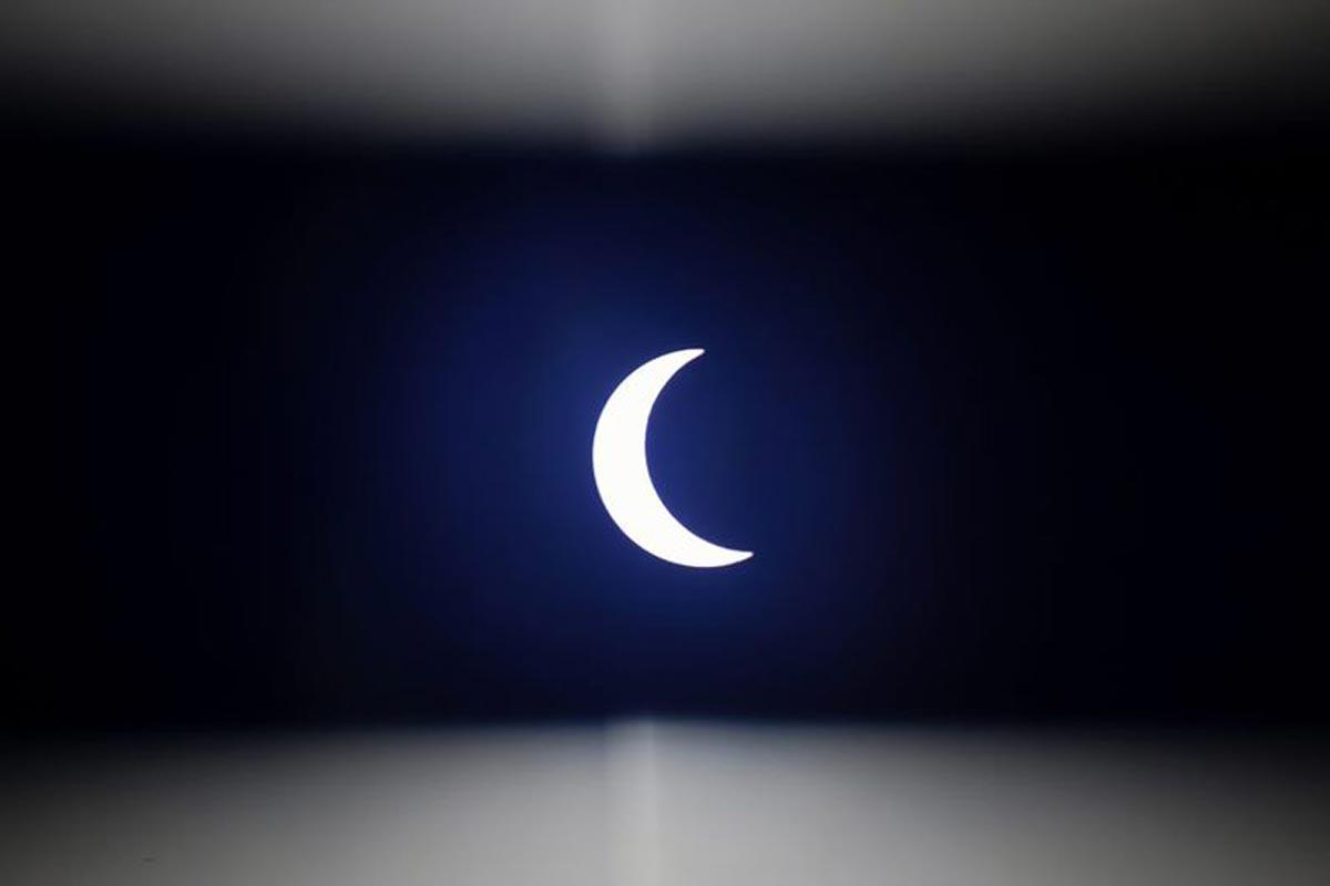 La lune se déplace devant le soleil, vue à travers une bande de plastique sombre, pendant l'éclipse solaire annulaire vue de l'extérieur de Hanoi.