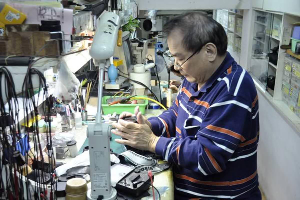 Un spécialiste, réparant un vieux Nikon dans son atelier.