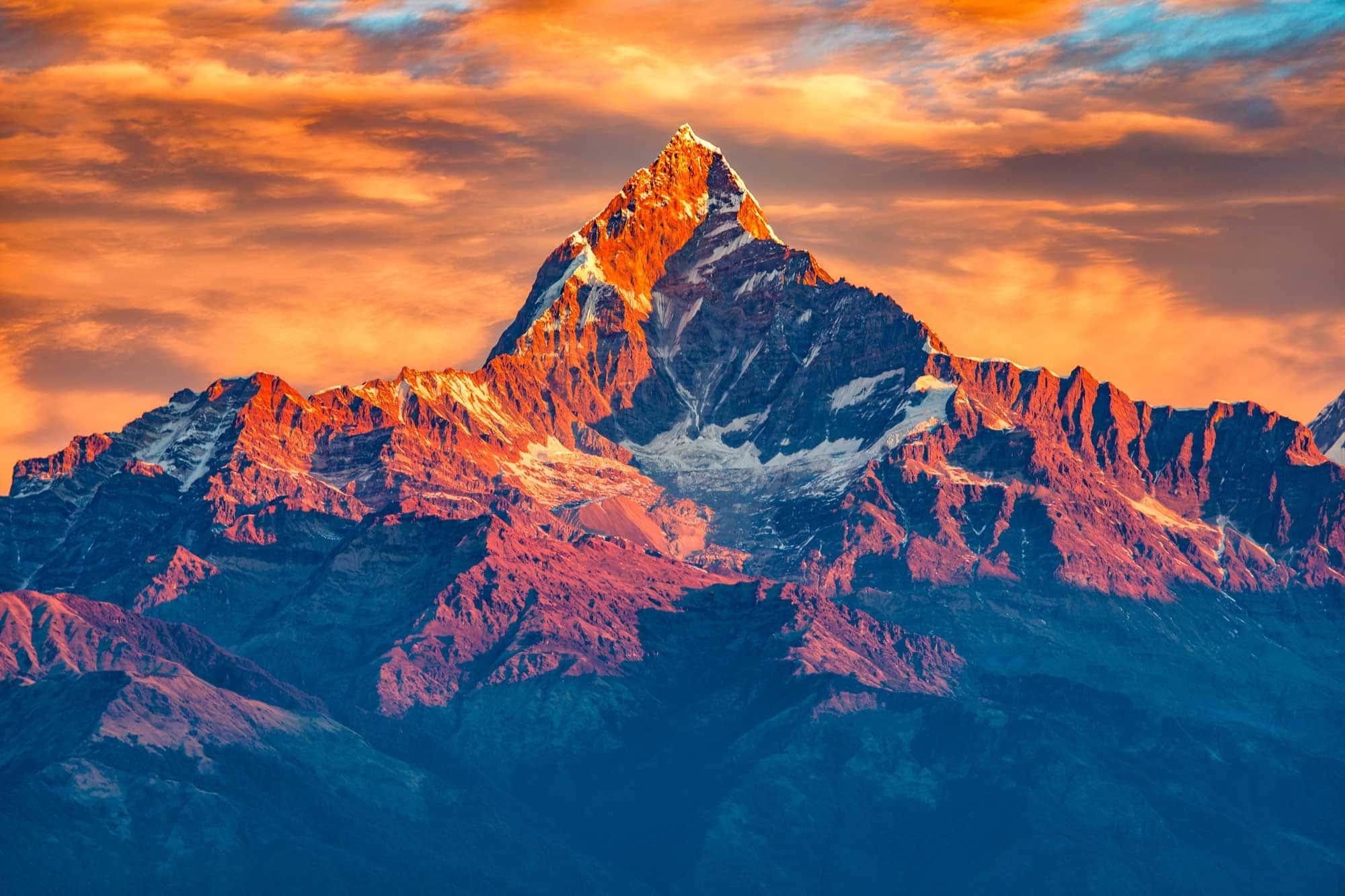 Magnifique lever de soleil nuageux dans les montagnes avec la crête de neige